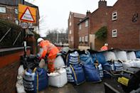 Local council employees use sandbags to prepare flood defences in a street in York, northern England, on January 19, 2021 as Storm Christoph brings heavy rains across England. (Photo by Paul ELLIS / AFP) (Photo by PAUL ELLIS/AFP via Getty Images)