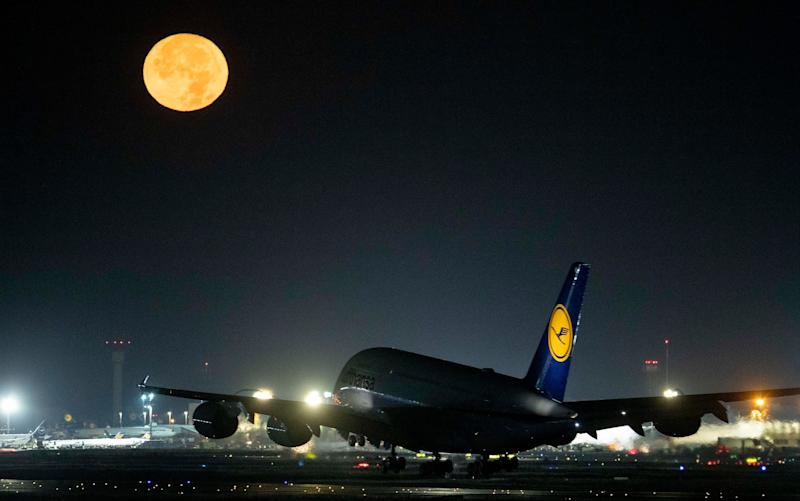 A Lufthansa A380 aircraft lands as the Hunter's Moon shines at the international airport in Frankfurt, Germany, on Sunday October 13.  - AP