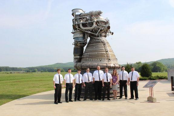 Engineers dressed in Apollo-style white shirts and thin black ties stand by an F-1 engine at NASA's Marshall Space Flight Center in Huntsville, Ala.
