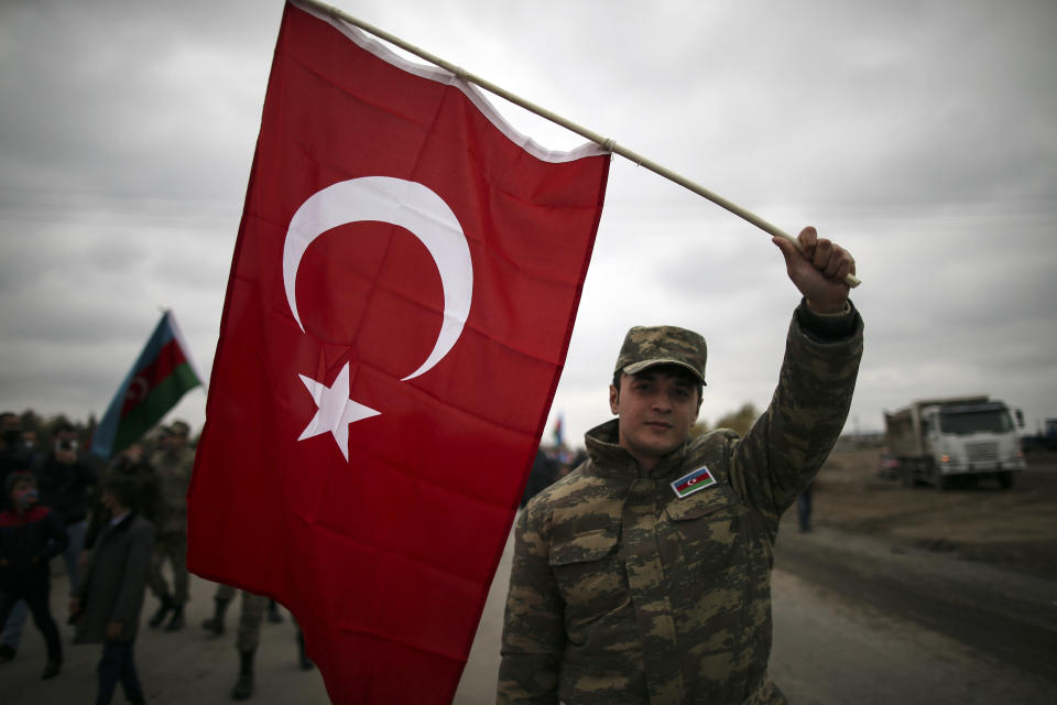 An Azerbaijani soldier holds a Turkish national flag as he celebrates the transfer of the Lachin region to Azerbaijan's control, as part of a peace deal that required Armenian forces to cede the Azerbaijani territories they held outside Nagorno-Karabakh, in Aghjabadi, Azerbaijan, Tuesday, Dec. 1, 2020. Azerbaijan has completed the return of territory ceded by Armenia under a Russia-brokered peace deal that ended six weeks of fierce fighting over Nagorno-Karabakh. Azerbaijani President Ilham Aliyev hailed the restoration of control over the Lachin region and other territories as a historic achievement. (AP Photo/Emrah Gurel)