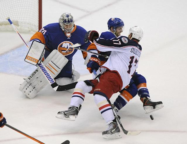 New York Islanders' Andrew MacDonald, center, fights with Columbus Blue Jackets' Brandon Dubinsky (17) as Islanders goalie Evgeni Nabokov (20) stands guard during the first period of an NHL hockey game on Saturday, Oct. 5, 2013, in Uniondale, N.Y. (AP Photo/Kathy Kmonicek)