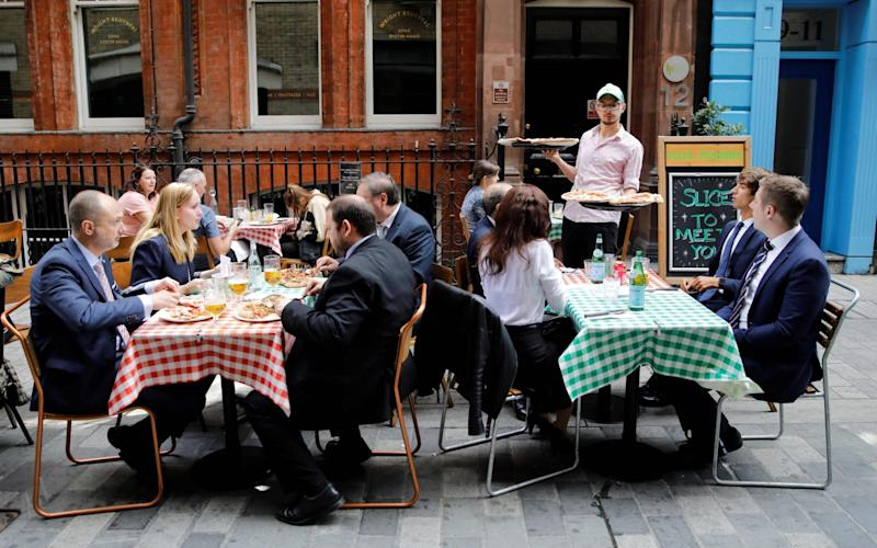 A waiter serves pizzas as diners sit at tables outside a restaurant in London on August 3 - TOLGA AKMEN/AFP