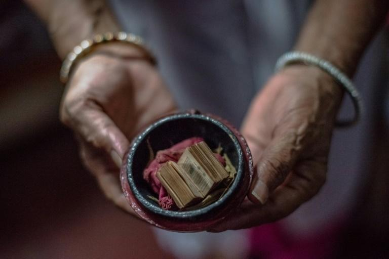 Shah Jahan Begum, 65, the wife of Indian Partition survivor Saleem Hasan Siddiqui, poses for a photograph with a miniature Koran his family saved during Partition at the home where he has lived since Partition in New Delhi
