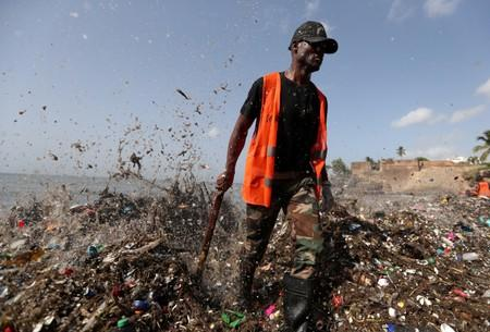 FILE PHOTO: A soldier walks on the shores of Montesinos beach, which is covered in plastic and other debris, during a cleanup in Santo Domingo