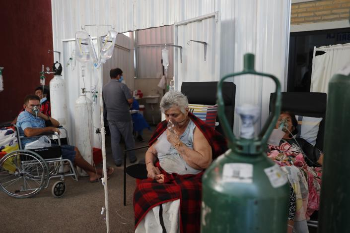Patients breathe from oxygen tanks as they wait for a bed to open in the COVID-19 treatment area of the hospital in Villa Elisa, Paraguay, Tuesday, April 20, 2021. (AP Photo/Jorge Saenz)