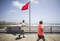 Patrons of the Bogue Inlet Pier in Emerald Isle, N.C. walk past a red flag signaling hazardous swimming conditions as Tropical Storm Isaias approaches the southeast on Sunday, Aug. 2, 2020. (Julia Wall/The News & Observer via AP)