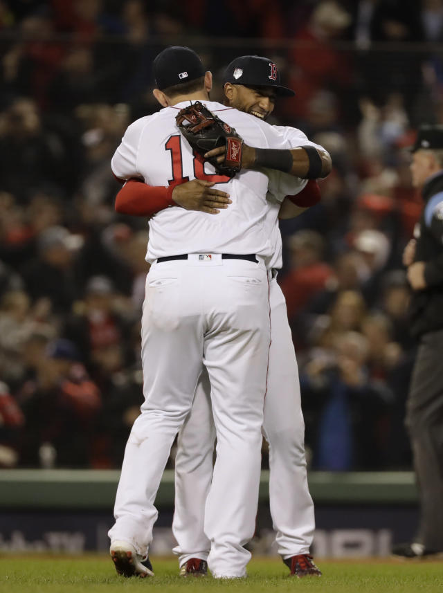 Boston Red Sox's Mitch Moreland, left, hugs Eduardo Nunez after Game 1 of the World Series baseball game Tuesday, Oct. 23, 2018, in Boston. The Red Sox won 8-4 to take a 1-0 lead in the series. (AP Photo/David J. Phillip)