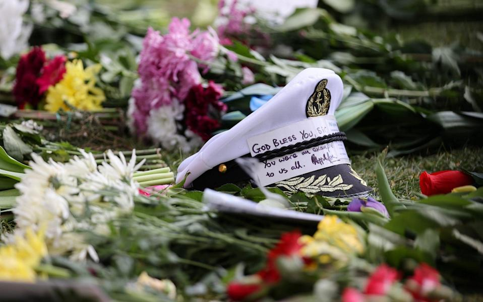 A captain's cap with message of condolence on flowers left outside of Windsor Castle on April 11, 2021 in Windsor, England