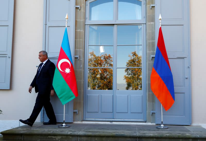 FILE PHOTO: A security guard walks past an Azerbaijan (L) and Armenian flag at the opening of talks in Geneva