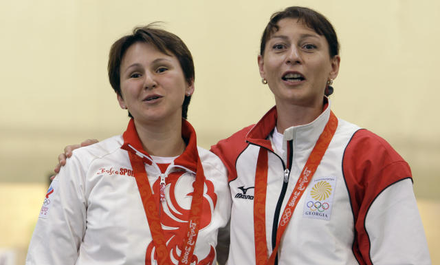 FILE - In this Sunday, Aug. 10, 2008 file photo, Russia's Natalia Paderina, left, and Georgia's Nino Salukvadze embrace after the women's 10 meter air pistol final at the Beijing 2008 Olympics in Beijing. Even if it takes an extra year, Salukvadze will still be aiming for an Olympic record. The Georgian shooter has competed at every Olympics since 1988, where she won a gold medal for the Soviet Union. At the Tokyo Olympics now postponed until 2021 because of the coronavirus pandemic she will set a women's record of nine appearances. (AP Photo/Sergey Ponomarev, file)