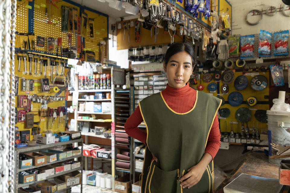 Portrait of young latin entrepreneur woman with retail business background.