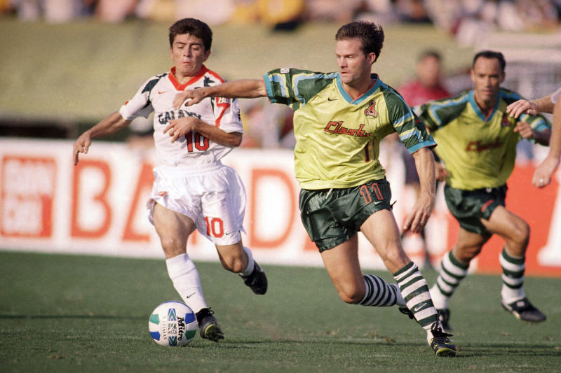 """FILE - In this Sept. 15, 1996, file photo, Los Angeles Galaxy's Mauricio Cienfuegos (10) pursues San Jose Clash's Eric Wynalda during the first half of an MLS soccer game at the Rose Bowl in Pasadena, Calif. Before the first-ever Major League Soccer match on April 6, 1996, a group of Clash players went to a trendy San Jose restaurant for some pre-game bonding, and four of them threw up after the meal. But it had nothing to do with the food, recalled Wynalda. """"It was just the nervousness,"""" he said. These were guys that had never played in a professional game."""" (AP Photo/Michael Caulfield, File)"""