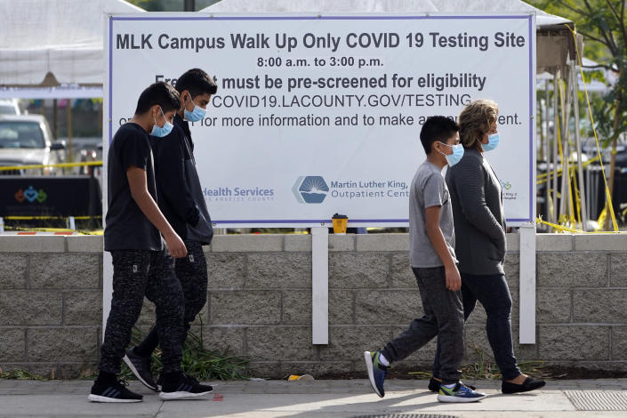 Masked pedestrians walk past a COVID-19 testing site on the Martin Luther King Jr. Medical Campus Thursday, Jan. 7, 2021, in Los Angeles. (AP Photo/Marcio Jose Sanchez)