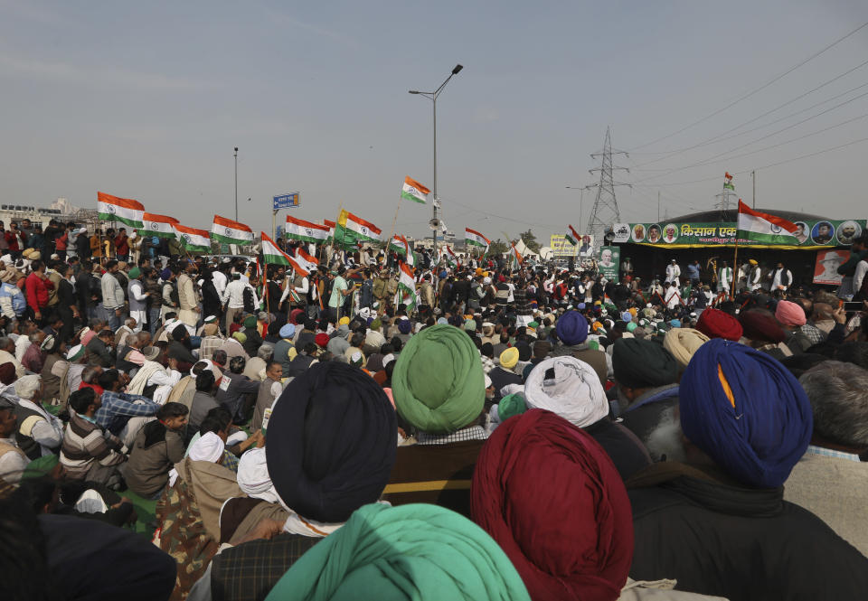 Farmers listen to their leaders during a day-long hunger strike as they continue to protest against three farm laws at the Delhi-Uttar Pradesh border, in New Delhi, India, Saturday, Jan. 30, 2021. Indian farmers and their leaders spearheading more than two months of protests against new agriculture laws began a daylong hunger strike Saturday, directing their fury toward Prime Minister Narendra Modi and his government. Farmer leaders said the hunger strike, which coincides with the death anniversary of Indian independence leader Mahatma Gandhi, would reaffirm the peaceful nature of the protests. (AP Photo/Manish Swarup)