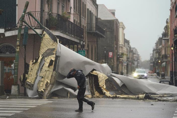 A man passes by a section of roof that was blown off of a building in the French Quaeter by Hurricane Ida winds, Sunday, Aug. 29, 2021, in New Orleans.