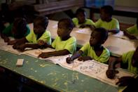 In this Nov. 13, 2013 photo, children attend class in the U.S.-based Church of Bible Understanding orphanage in Kenscoff, Haiti. The orphanage is run by a Christian missionary group funded by the Olde Good Things antique store on Manhattan's Upper West Side. While many other orphanages also have failed the Caribbean country's new national standards, and conditions are far worse in some, the group's three-story building on the hilly outskirts of Port-au-Prince stands out because it's run by an organization with such an unusual, and successful fundraising operation. The failure to meet the standards would seem to contradict their financial position.(AP Photo/Dieu Nalio Chery)
