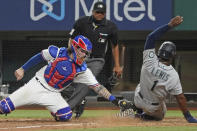 Seattle Mariners base runner Kyle Lewis is tagged out at home by Texas Rangers catcher Jonah Heim to end a baseball game in the ninth inning Saturday, May 8, 2021, in Arlington, Texas. (AP Photo/Louis DeLuca)