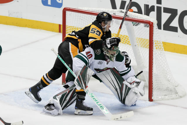 Pittsburgh Penguins' Jake Guentzel (59) crashes into Minnesota Wild goaltender Devan Dubnyk during the first period of an NHL hockey game Thursday, Dec. 20, 2018, in Pittsburgh. (AP Photo/Keith Srakocic)