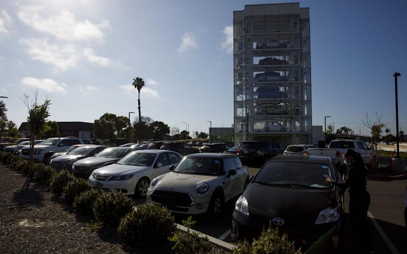 row of pre-registered cars at auto delaership - Patrick Fallon/Bloomberg