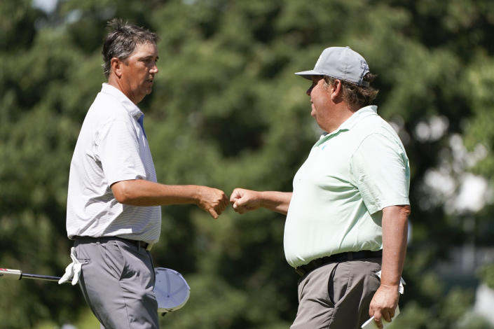 Shane Bertsch fist bumps Tim Herron, right, after making a birdie putt on the 18th green during the second round of the PGA Tour Champions Principal Charity Classic golf tournament, Saturday, June 5, 2021, in Des Moines, Iowa. (AP Photo/Charlie Neibergall)