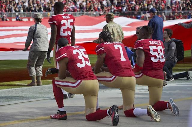 Quarterback Colin Kaepernick, safety Eric Reid, and linebacker Eli Harold of the San Francisco 49ers kneel before a game against the New Orleans Saints in Santa Clara, Calif on Nov. 6, 2016. (AFP Photo/BRIAN BAHR)