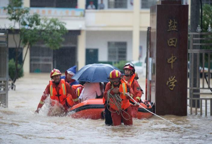 Rescue workers evacuate students stranded by floodwaters at a school, amid heavy rainfall in Duchang county