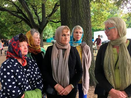 Robyn Molony (R), 65, wears a headscarf with her friends as they take their regular walk opposite Al Noor mosque in Christchurch, New Zealand, March 22, 2019. REUTERS/Tom Westbrook