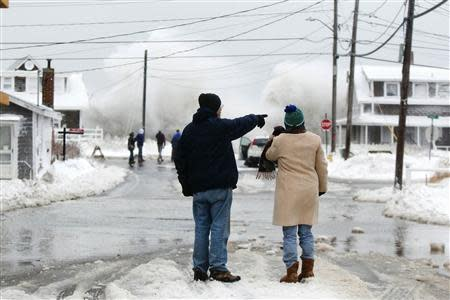Two people watch the waves crash in the distance during a winter nor'easter snow storm in Scituate, Massachusetts January 3, 2014. REUTERS/Dominick Reuter