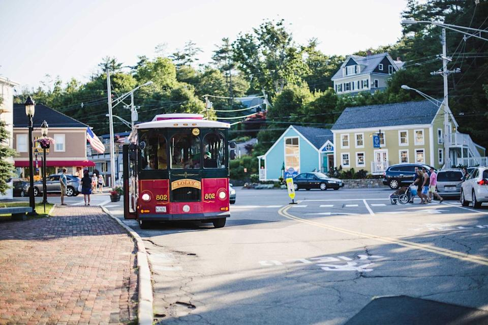 Vintage bus, people walking and cars in the street of Ogunquit, a pretty village on the east coa