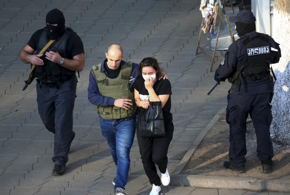 """Georgian police officers escorts a woman who escaped from a bank where an armed assailant has taken several people hostage, in the town of Zugdidi in western Georgia, Wednesday, Oct. 21, 2020. An armed assailant took several people hostage at a bank in the ex-Soviet nation of Georgia on Wednesday, authorities said. The Georgian Interior Ministry didn't immediately say how many people have been taken hostage in the town of Zugdidi in western Georgia, or what demands the assailant has made. Police sealed off the area and launched an operation """"to neutralize the assailant,"""" the ministry said in a statement. (AP Photo/Zurab Tsertsvadze)"""