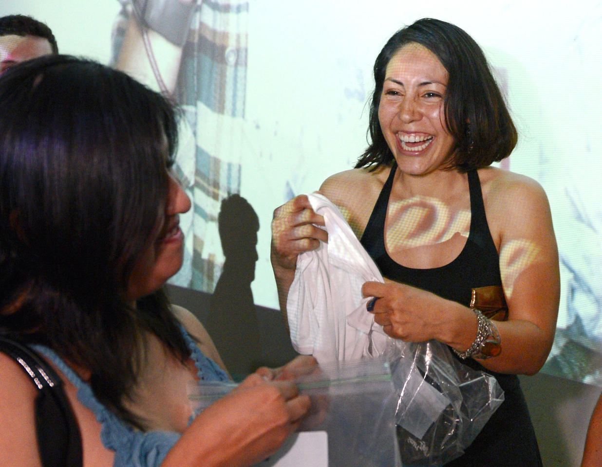 Karen Arellano, right, laughs as she smells shirts with her friend Christina Lopez during a pheromone party, Friday, June 15, 2012, in Los Angeles. The get-togethers, which have been held in New York and Los Angeles and are planned for other cities, require guests to submit a slept-in T-shirt that will be sniffed by other participants. Then you can pick your partner based on scent. (AP Photo/Mark J. Terrill)