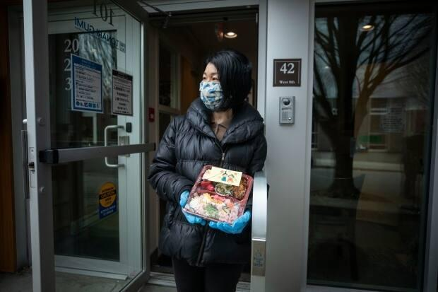 Keiko Funahashi carries one of  the bento boxes she delivers to Japanese seniors in Metro Vancouver each week. (Ben Nelms/CBC - image credit)