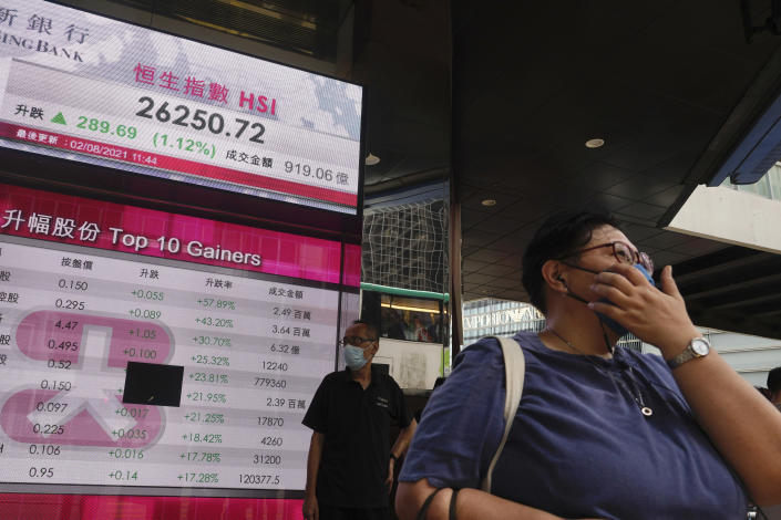 A woman walks past a bank's electronic board showing the Hong Kong share index at Hong Kong Stock Exchange in Hong Kong Monday, Aug. 2, 2021. Asian stocks have started the week higher, even as China reported a slowdown in manufacturing activity and countries in the region continue to be hammered by the delta variant. (AP Photo/Vincent Yu)
