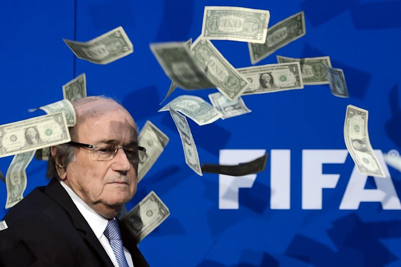 A prankster showers Sepp Blatter with fake dollars at FIFA headquarters in July 2015 (AFP Photo/Fabrice Coffrini)