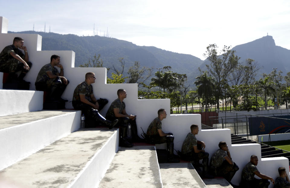Brazil Army soldiers sit on the shadow to watch the Netherlands national soccer team training session ahead of the 2014 World Cup in Rio de Janeiro June 8, 2014.   REUTERS/Ricardo Moraes (BRAZIL  - Tags: SPORT SOCCER WORLD CUP)