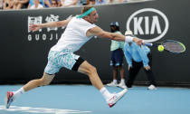 Tennys Sandgren of the U.S. makes a backhand return to Italy's Matteo Berrettini during their second round singles match at the Australian Open tennis championship in Melbourne, Australia, Wednesday, Jan. 22, 2020. (AP Photo/Andy Wong)