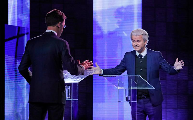 Right-wing populist leader Geert Wilders gestures as he talks to Dutch Prime Minister Mark Rutte, left, during a national televised debate - Credit: AP