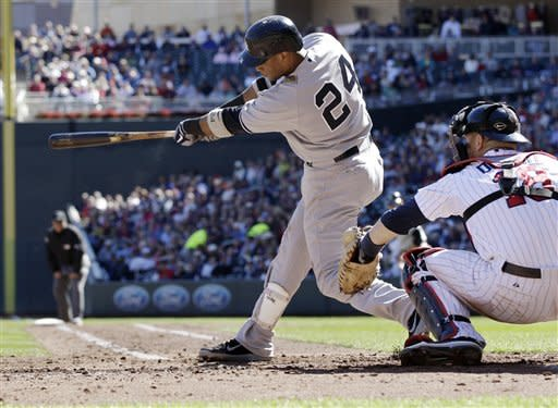 New York Yankees' Robinson Cano hits a two-run double in the third inning of a baseball game off Minnesota Twins pitcher Brian Duensing on Wednesday, Sept. 26, 2012 in Minneapolis. Catching is Twins' Ryan Doumit, right. (AP Photo/Jim Mone)