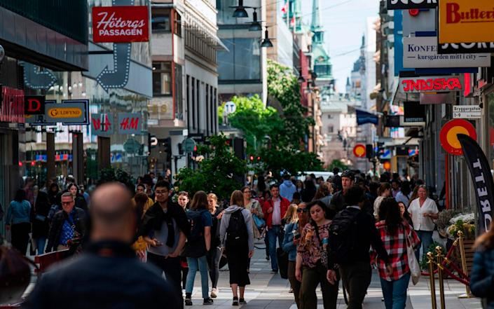 People walk in Drottninggatan during rush hour in Stockholm, amid the pandemic - AFP