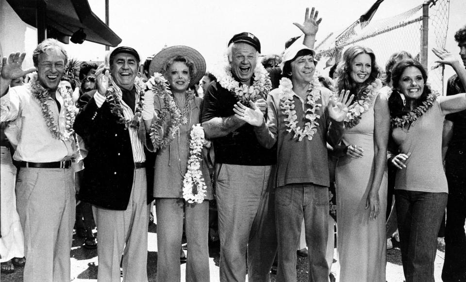 "FILE - This Oct. 2, 1978 file photo shows the cast of ""Gilligan's Island,"" from left, Russell Johnson, as the professor; Jim Backus as Thurston Howell III; Natalie Schafer, as Mrs. Howell III; Alan Hale Jr., as the skipper; Bob Denver, as Gilligan; Judith Baldwin replacing original cast member Tina Louise, as Ginger, and Dawn Wells, as Mary Ann, posing during filming of a two-hour reunion show, ""The Return from Gilligan's Island,"" in Los Angeles. Wells, who played the wholesome Mary Ann among a misfit band of shipwrecked castaways on the 1960s sitcom ""Gilligan's Island, died Wednesday, Dec. 30, 2020, of causes related to COVID-19, her publicist said. (AP Photo/Wally Fong, File)"