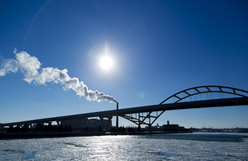 Steam is seen drifting from a factory over the Hoan Bridge as another round of arctic air blasts the midwest keeping the wind chill in the negative numbers, in Milwaukee, Wisconsin February, 6, 2014. REUTERS/Darren Hauck (UNITED STATES - Tags: ENVIRONMENT)