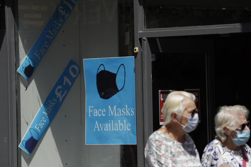 People walk past a sign advertising face masks for sale in a shop window in Kingston upon Thames, south west London, Monday, June 22, 2020. The two-metre social distancing rule will be under review as the UK relax coronavirus lockdown measures implemented to stem the spread of the virus. (AP Photo/Matt Dunham)