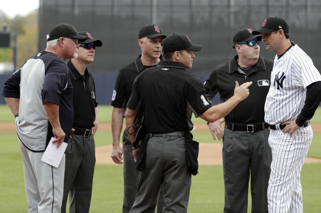 New York Yankees manager Aaron Boone, right, and Detroit Tigers manager Ron Gardenhire, left, meet with the umpires before a baseball spring exhibition game, Friday, Feb. 23, 2018, in Tampa, Fla. Boone is managing his first baseball game at any level. (AP Photo/Lynne Sladky)