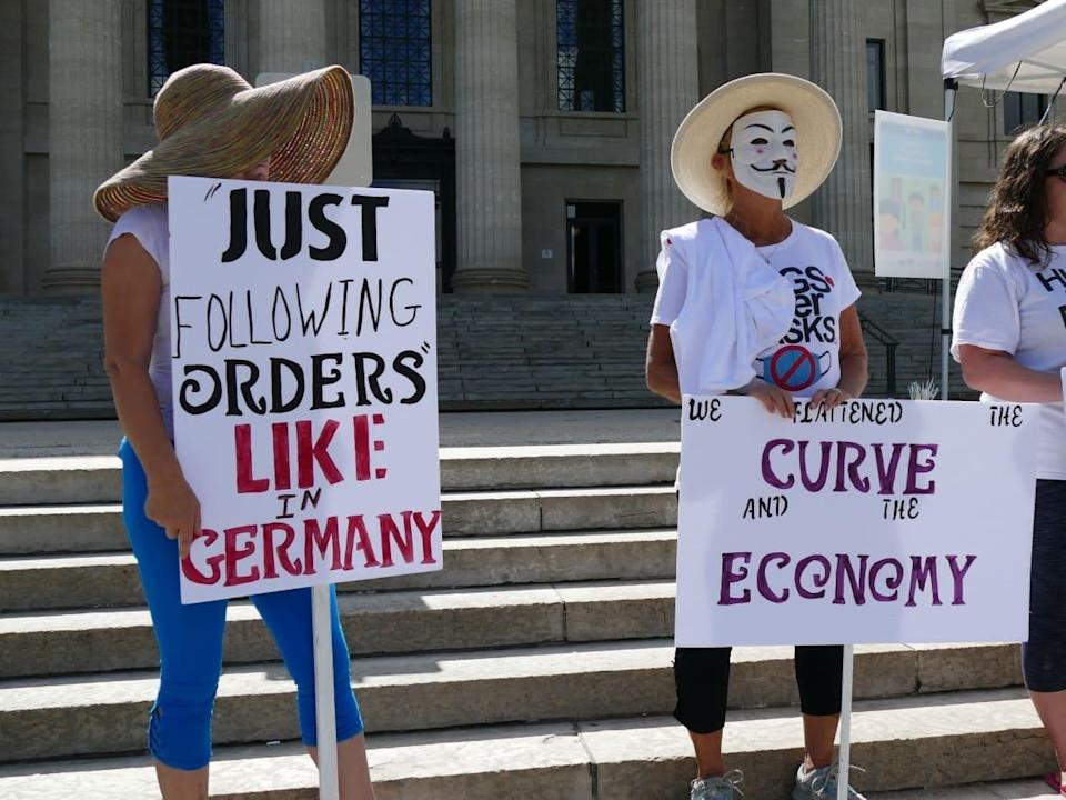 Protesters are seen holding masks at an anti-mask rally at the Manitoba legislature in Winnipeg in August 2020, including one sign that equates public health orders with Nazism. Comparisons to the Nazi era are becoming a common sight at demonstrations against public health measures aimed at containing the spread of COVID-19. (Jaison Empson/CBC - image credit)