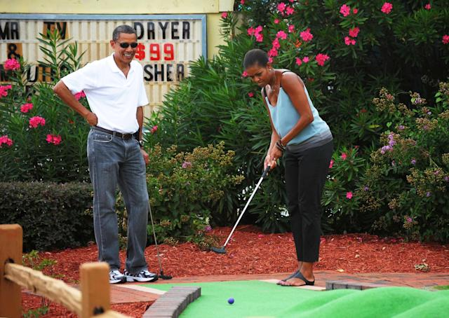 President Barack Obama watches as first lady Michelle Obama putts during a round of mini golf at Pirate's Island Golf on Aug. 14, 2010 in Panama City Beach, Florida.