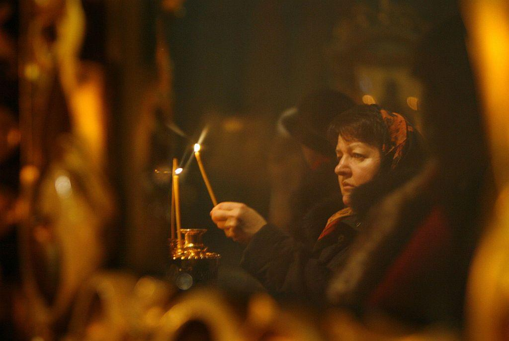 RUSSIA: Believers place lit candles during an Orthodox Christmas eve service in a church in the southern Russian city of Rostov-on-Don January 6, 2013. Orthodox Christians mark Christmas according to the Julian calendar on January 7.