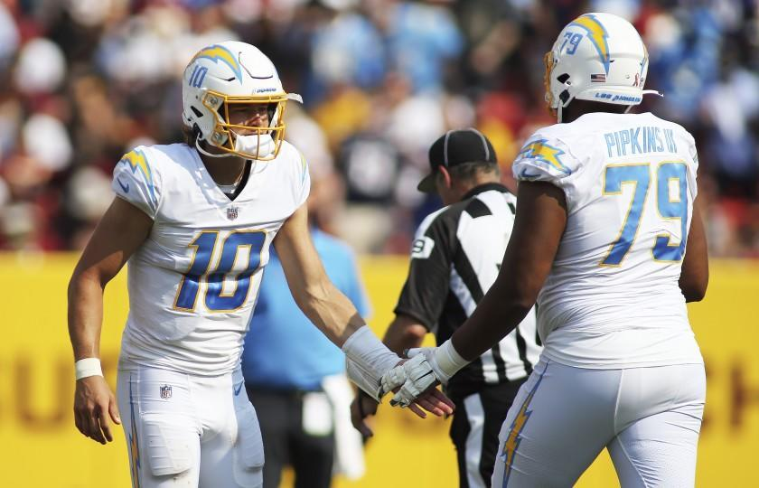 Los Angeles Chargers quarterback Justin Herbert (10) and Los Angeles Chargers offensive tackle Trey Pipkins.