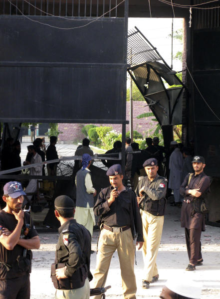 """Pakistani police officers examine the main gate of a central jail in Bannu, 170 kilometer (106 miles) south of Peshawar, Pakistan on Sunday, April 15, 2012. Taliban militants battled their way into the prison in northwest Pakistan on Sunday, freeing close to 400 prisoners, including at least 20 described by police as """"very dangerous"""" insurgents, authorities and the militants said. (AP Photo Ijaz Muhammad)"""