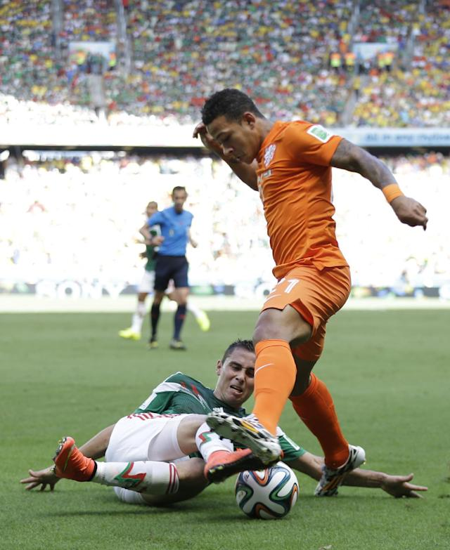 Netherlands' Memphis Depay, top, is challenged by Mexico's Paul Aguilar during the World Cup round of 16 soccer match between the Netherlands and Mexico at the Arena Castelao in Fortaleza, Brazil, Sunday, June 29, 2014. (AP Photo/Natacha Pisarenko)