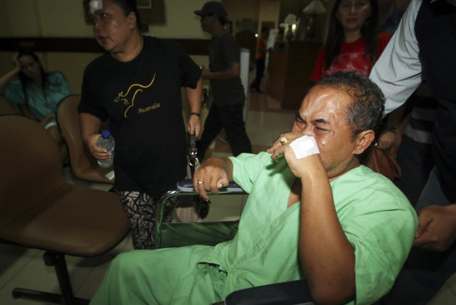 A passenger injured in a plane crash in a wheelchair is carried for a madical treatment at a hospital in Jimbarn, Bali, Indonesia, Saturday, April 13, 2013. A Lion Air plane carrying more than 100 passengers and crew overshot a runway on the Indonesian resort island of Bali on Saturday and crashed into the sea, injuring nearly two dozen people, officials said. (AP Photo/Firdia Lisnawati)